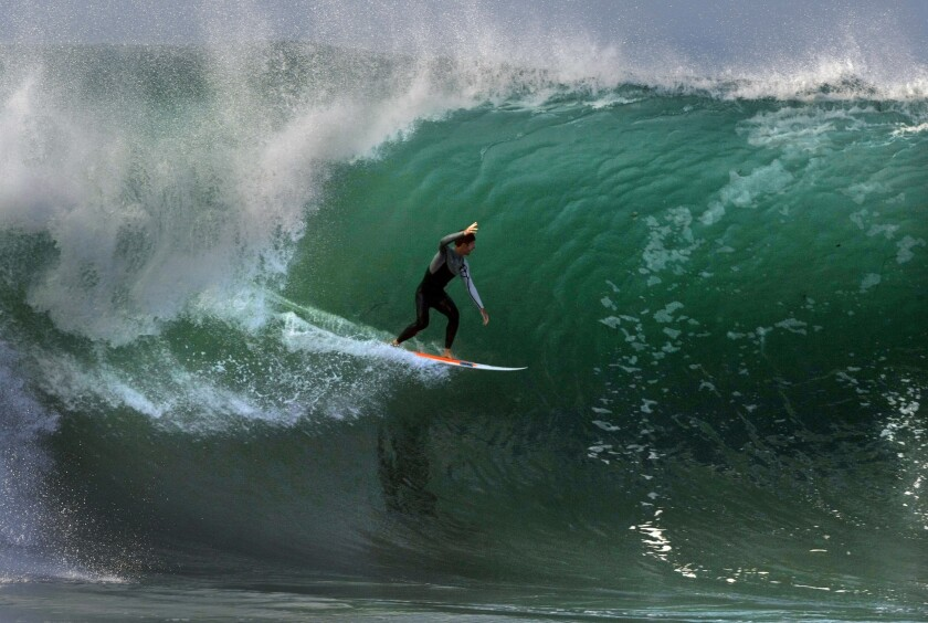 A surfer raises his arm to acknowledge a screaming crowd at the Wedge in Newport Beach. Thousands of spectators lined the beach Wednesday to watch waves as high as 25 feet tall generated by Hurricane Marie off the Pacific coast.