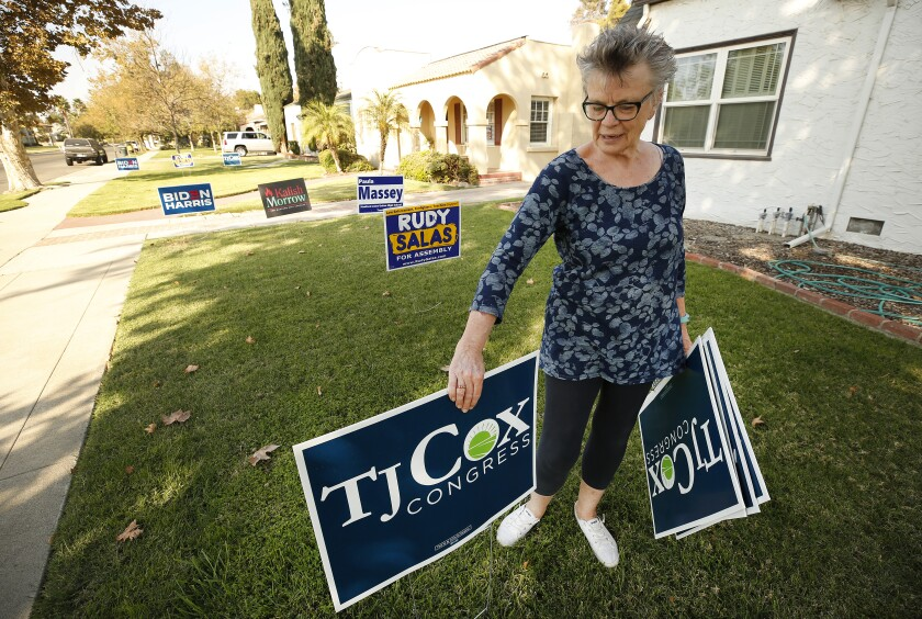 Cathy Jorgensen, chair of the Kings County Democratic Central Committee, places signs outside her Hanford, Calif., home.