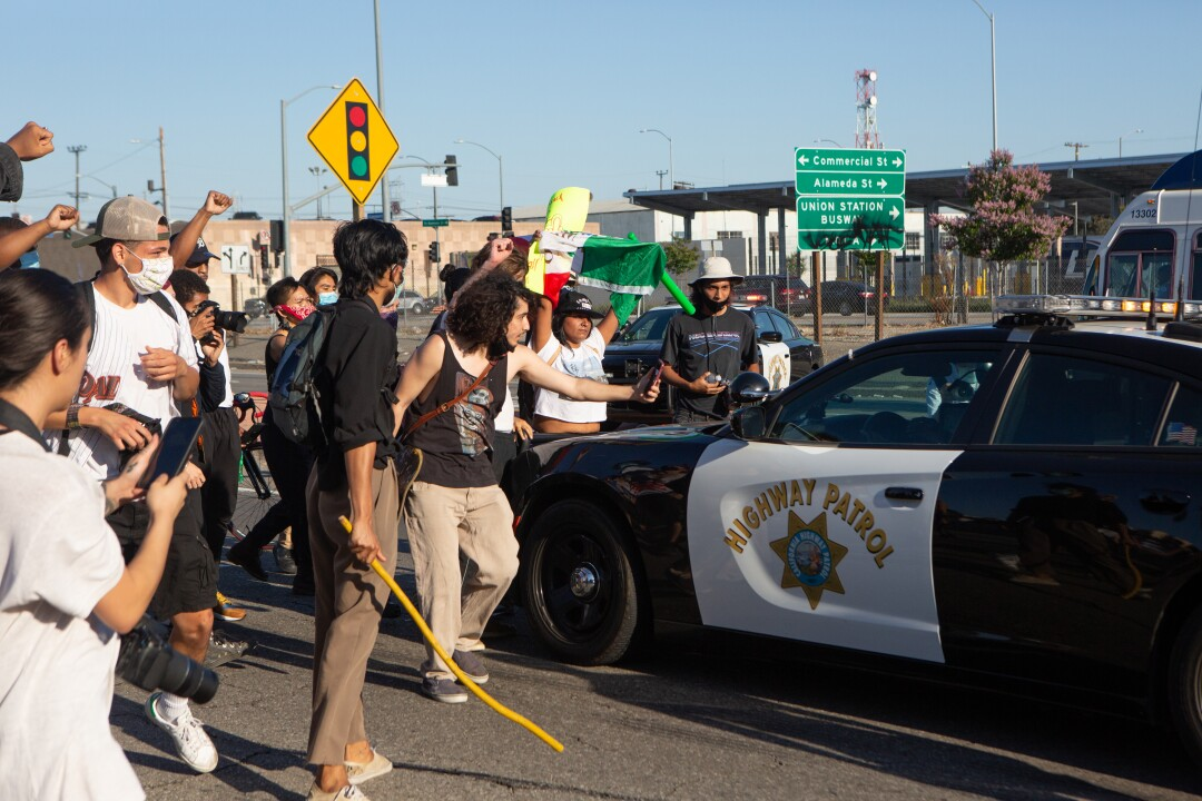 Protesters surround a California Highway Patrol cruiser in downtown Los Angeles