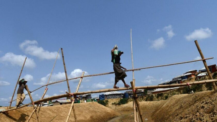 Rohingya men carry sandbags to fortify shelters in preparation for the monsoon season in Kutupalong refugee camp in southern Bangladesh.