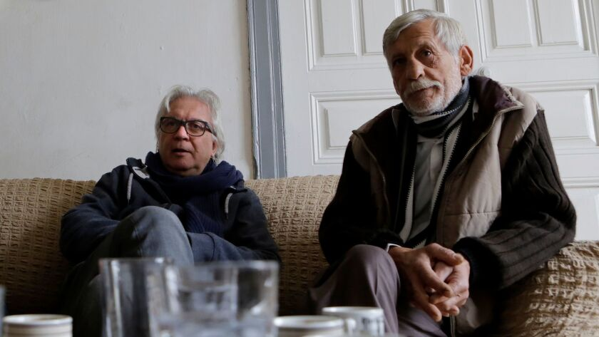 Greek Cypriot Michalis Georgiades, left, and Turkish Cypriot Cumar Kamir sit and talk in the mud-brick house in Morphou that is the foundation of their friendship.