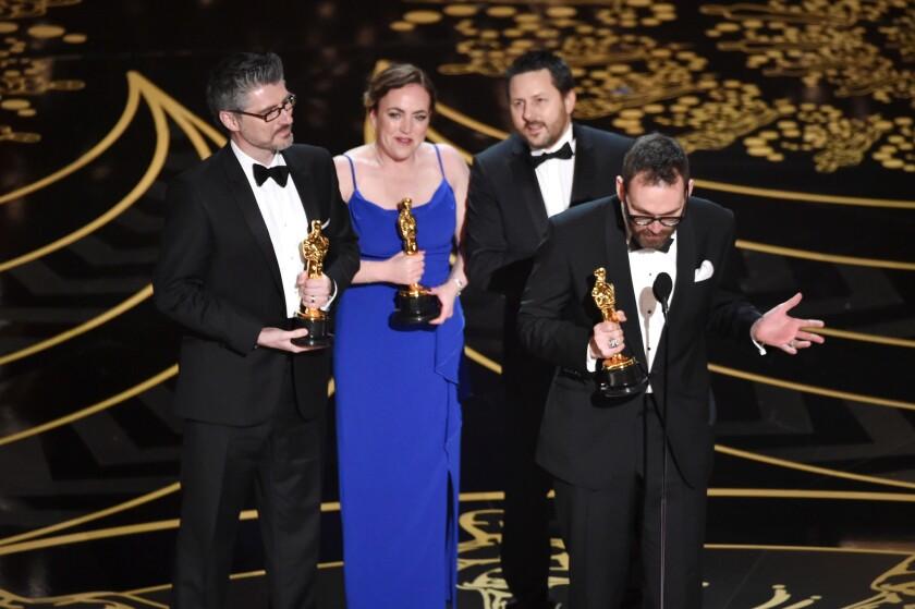 "From left, Mark Williams Ardington, Sara Bennett, Paul Norris, and Andrew Whitehurst accept the visual effects Oscar for ""Ex Machina."""