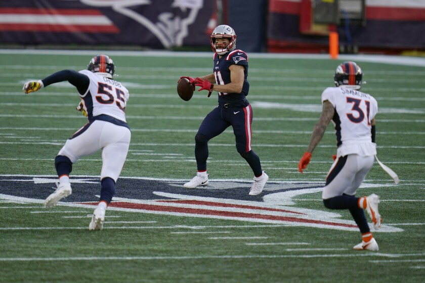 New England Patriots wide receiver Julian Edelman, center, looks for a receiver as he attempts to pass between Denver Broncos linebacker Bradley Chubb, left, and safety Justin Simmons, right, in the second half of an NFL football game, Sunday, Oct. 18, 2020, in Foxborough, Mass. (AP Photo/Charles Krupa)