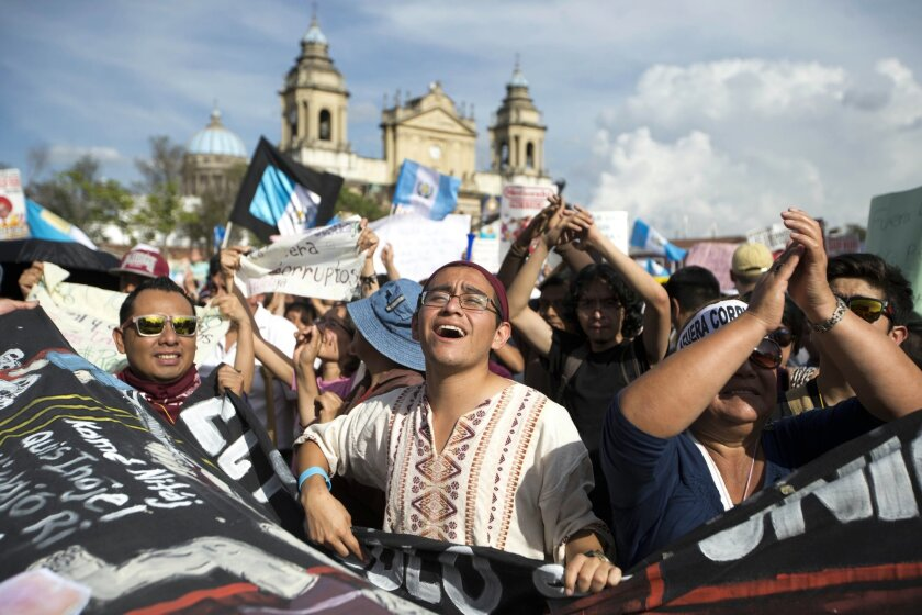 People chant slogans outside the National Palace during a protest demanding the resignation Guatemala's President Otto Perez Molina in Guatemala City, Saturday, May 30, 2015. Protesters are demanding the president step down after his Vice President Roxana Baldetti resigned earlier this month amid a corruption scandal. (AP Photo/Moises Castillo)