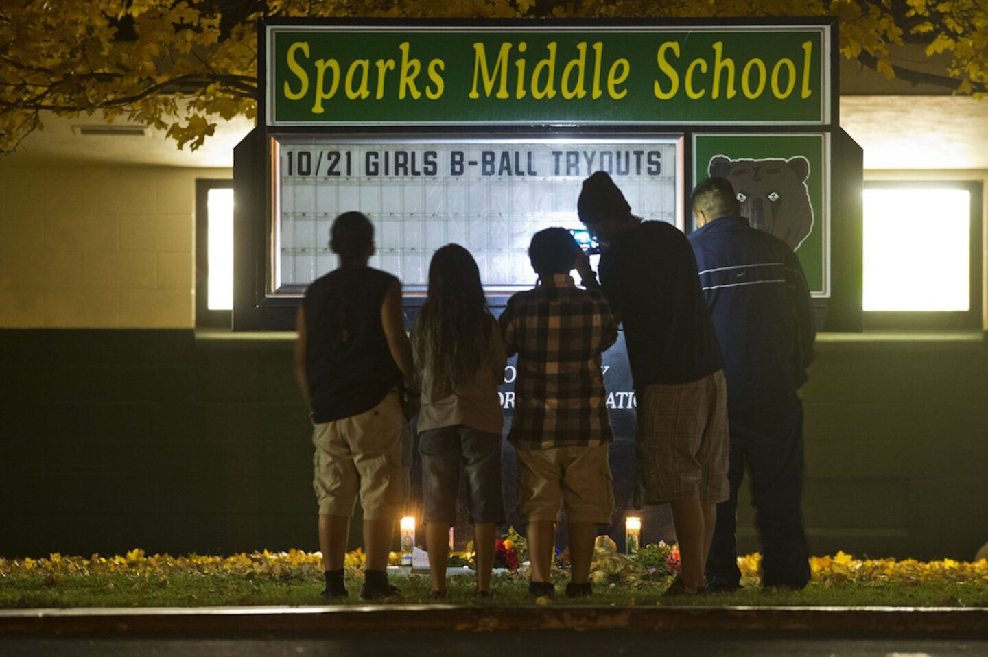 A family takes a photo of a memorial after a shooting at Sparks Middle School in Sparks, Nev.