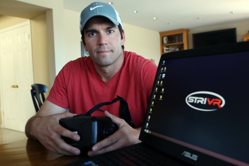 Derek Belch holding an oculus headset and the company logo for a virtual reality quarterback training system company on the computer screen. photo by Bill Wechter THE REPORTER WANTED THIS PHOTO FOR THE WEBSITE