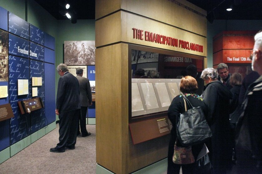 Visitors are seen looking at a display of President Abraham Lincoln's Emancipation Proclamation at the National Archives in Washington.