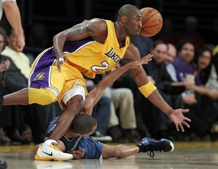 Los Angeles Lakers guard Kobe Bryant, top, and Minnesota Timberwolves guard Sebastian Telfair scramble for a loose ball during the first half of an NBA basketball game in Los Angeles, Tuesday, Nov. 9, 2010. (AP Photo/Jae C. Hong)