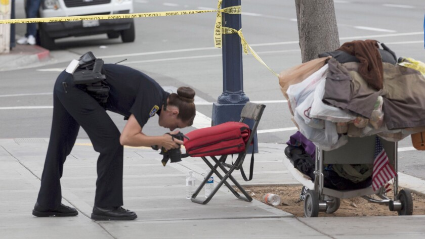 A San Diego police officer takes photos at the scene where a homeless man was attacked by a man with a hammer Wednesday morning.