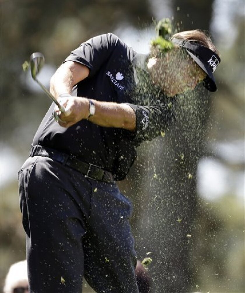 Phil Mickelson tees off on the first hole during the par three competition before the Masters golf tournament Wednesday, April 10, 2013, in Augusta, Ga. (AP Photo/Darron Cummings)