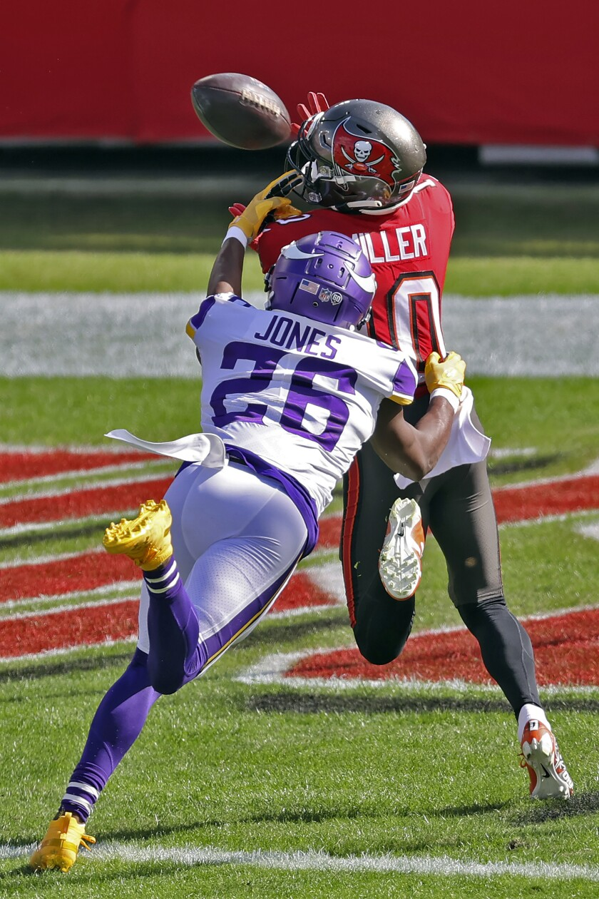Tampa Bay Buccaneers wide receiver Scott Miller (10) pulls in a 48-yard touchdown pass from Tom Brady after getting in front of Minnesota Vikings defensive back Chris Jones (26) during the first half of an NFL football game Sunday, Dec. 13, 2020, in Tampa, Fla. (AP Photo/Mark LoMoglio)