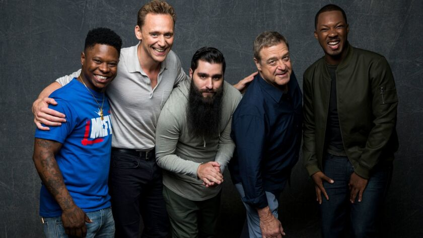"""The bearded Jordan Vogt-Roberts, center, with """"Kong: Skull Island"""" cast members, from left, Jason Mitchell and Tom Hiddleston; from right, Corey Hawkins and John Goodman at Comic-Con 2016,"""