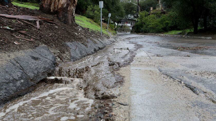 Water and debris flows down Country Club Drive in Burbank as rain continues to pound the Southland o