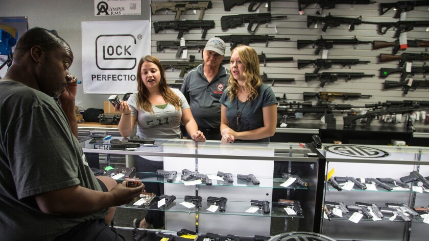 Store Managers Jamie Taflinger, left and Kendyll Murray show customer Cornell Hall, of Highland different types of ammo at the Get Loaded gun store on in Grand Terrace, CA.