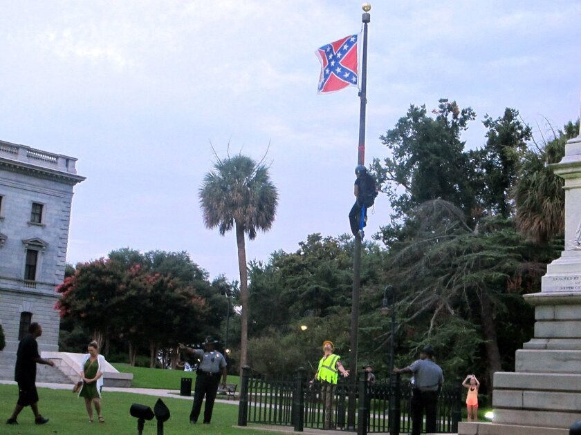 Police surround the flagpole flying the Confederate battle flag at a Confederate monument  at the Statehouse in Columbia, S.C., on Saturday, June, 27, 2015 as Bree Newsome of Charlotte, N.C. climbs the pole to remove the banner. She was taken into custody when she came down. The flag was raised aga