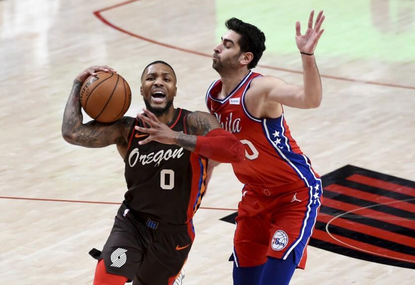 Portland Trail Blazers guard Damian Lillard, left, is fouled by Philadelphia 76ers guard Furkan Korkmaz during the first half of an NBA basketball game in Portland, Ore., Thursday, Feb. 11, 2021. (AP Photo/Steve Dykes)