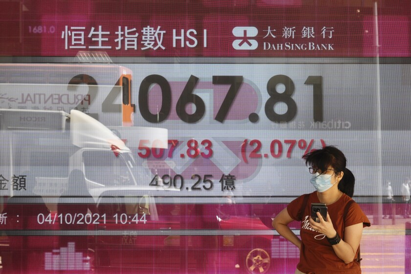 A woman walks past a bank's electronic board showing the Hong Kong share index at Hong Kong Stock Exchange in Hong Kong Monday, Oct. 4, 2021. Asian markets were mixed on Monday, while Hong Kong's benchmark shed more than 2% after troubled property developer China Evergrande's shares were suspended from trading. (AP Photo/Vincent Yu)