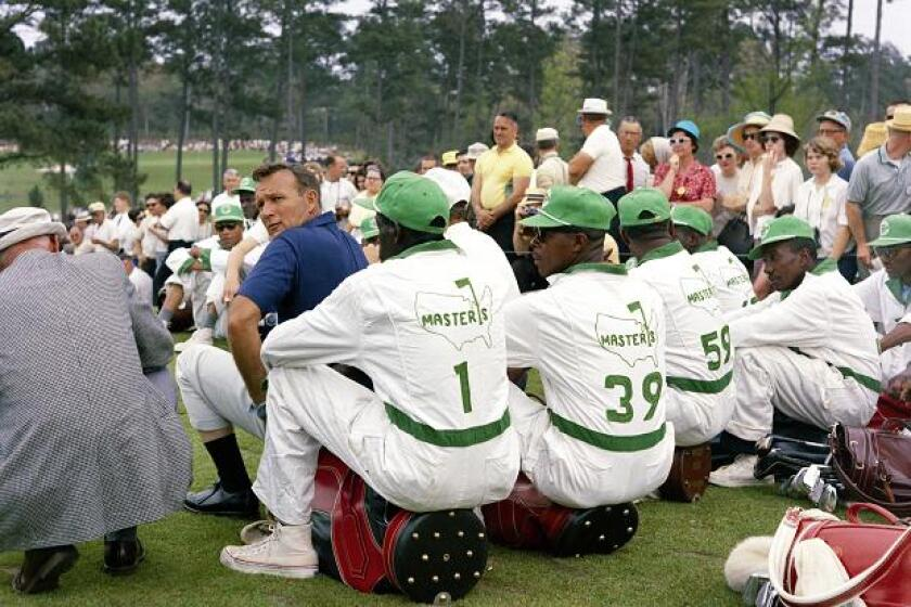 """In an image from the film, """"Loopers,"""" Arnold Palmer sits in front of a brigade of local Augusta caddies at the Masters."""