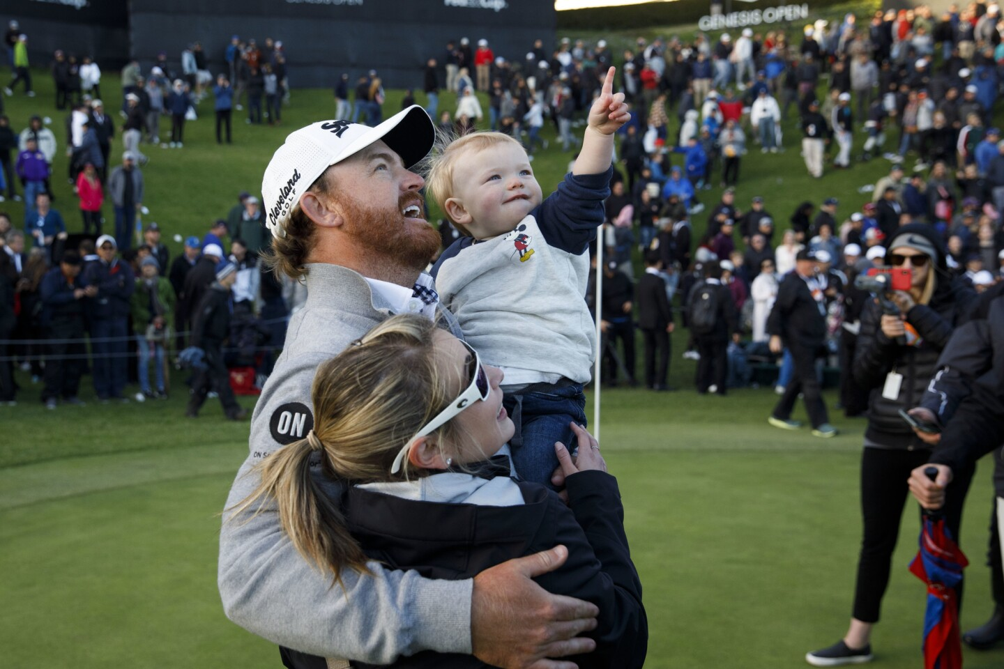 J.B. Holmes hugs his son Tucker and wife Erica after winning on the 18th hole the Genesis Open golf tournament at the Riviera Country Club.
