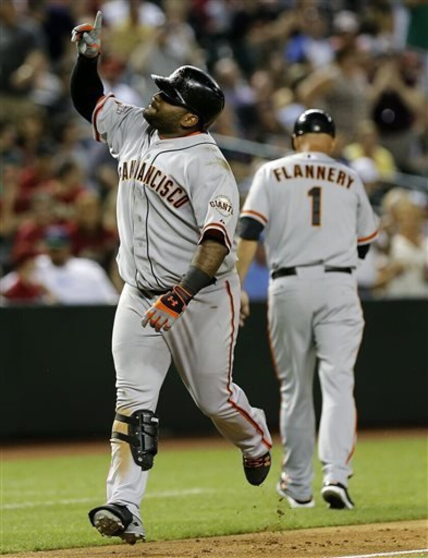San Francisco Giants' Pablo Sandoval points upward after hitting a two run home run against the Arizona Diamondbacks during the ninth inning of a baseball game, Tuesday, April 30, 2013, in Phoenix. At right is third base coach Tim Flannery. (AP Photo/Matt York)