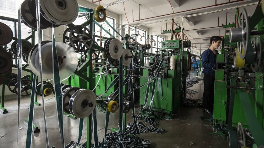 Polyvinyl chloride is fed into machines to make artificial Christmas tree branches at a factory in Yiwu, China, in October 2018.