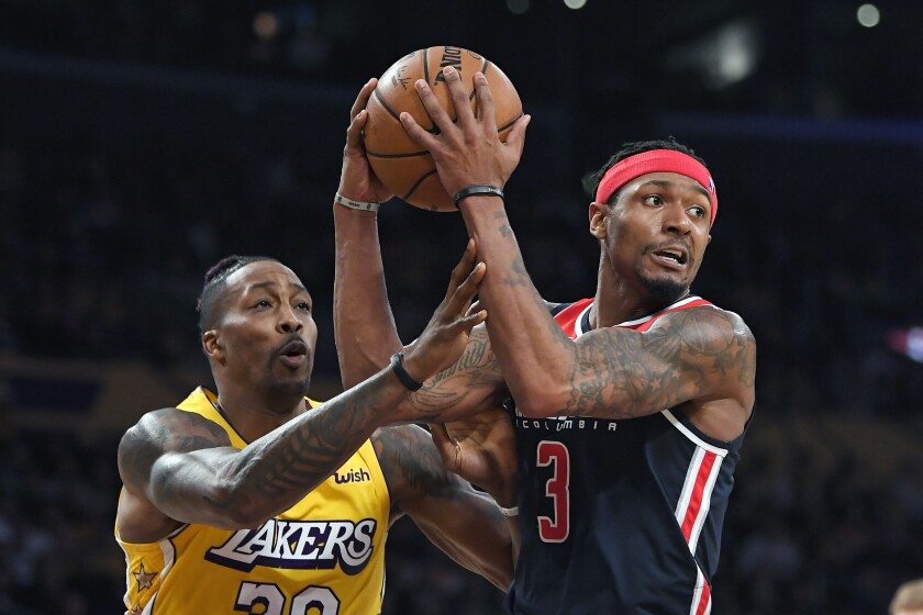 Wizards guard Bradley Beal tries to pass the ball while being defended by Lakers center Dwight Howard during a game Nov. 29.