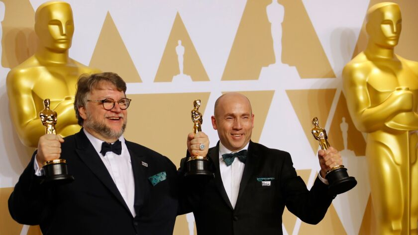 """Producer-director Guillermo del Toro and producer J. Miles Dale hold their best-picture Oscars for """"The Shape of Water,"""" at the 90th Academy Awards on Sundayat the Dolby Theatre in Hollywood. The movie was released by Fox Searchlight."""