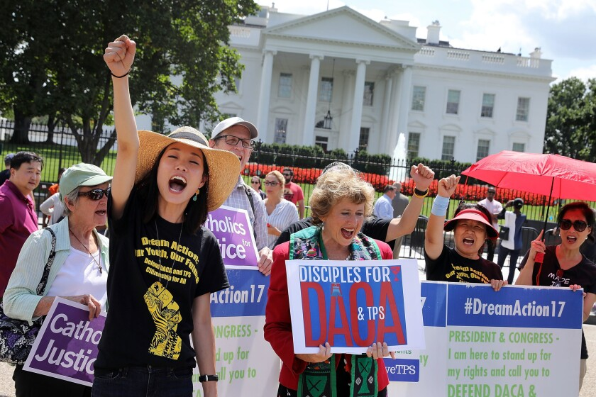 Serafina Ha, left, of Chicago and Sharon Stanley-Rea, director of the Disciples of Christ Refugee and Immigration Ministries, lead chants during a rally in favor of immigration reform in front of the White House August 30, 2017 in Washington, DC.