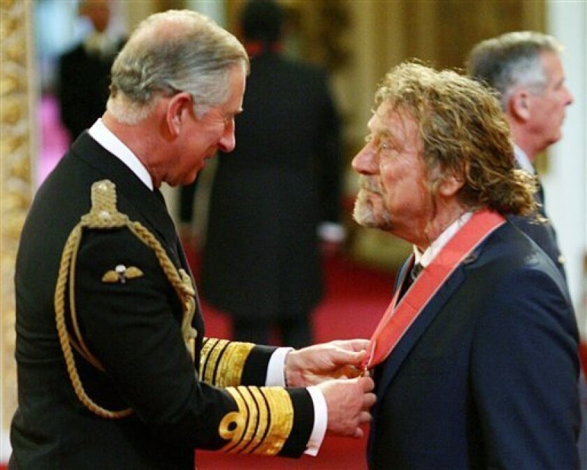Former Led Zeppelin frontman Robert Plant , right, receives his CBE from Britain's Prince Charles during the investiture ceremony at Buckingham Palace in London Friday July 10, 2009. (AP Photo/Johnny Green/Pool)