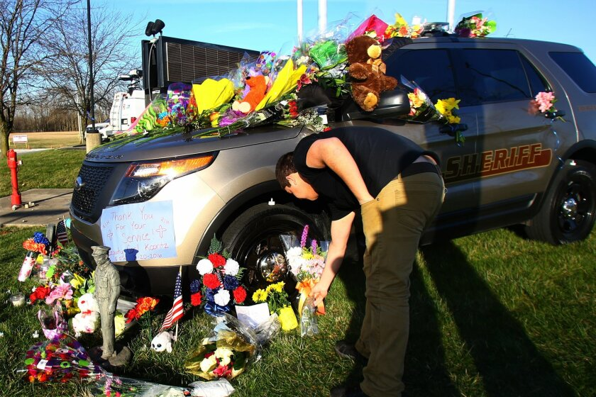Howard County Deputy Carl Koontz's patrol car sits in front of the Howard County Criminal Justice Center with black over the windshield Monday, March 21, 201, in Kokomo, Ind., as Blaine Duke drops flowers for Koontz, who was killed in the line of duty on Sunday, March 20, in Russiaville, Ind. (Tim Bath/The Kokomo Tribune via AP) MANDATORY CREDIT