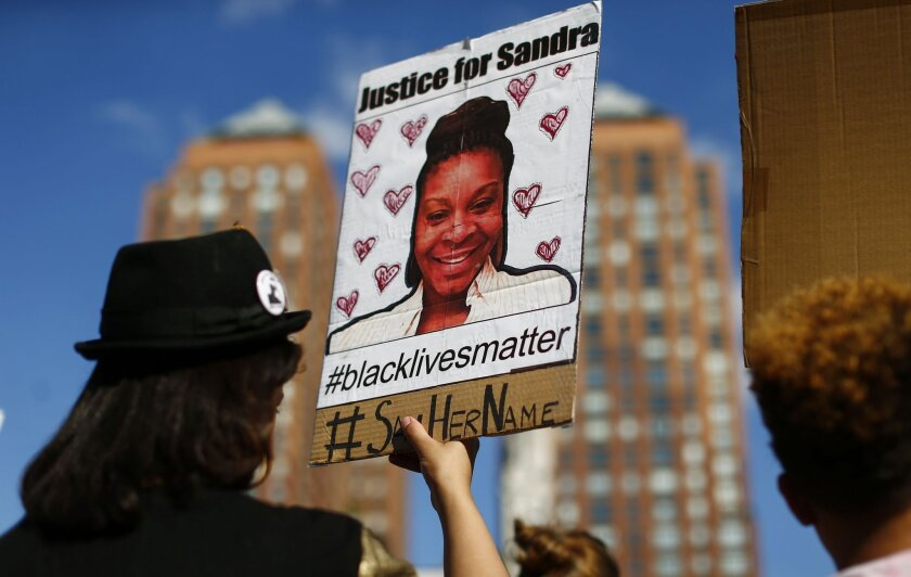 A woman holds a poster with a picture of Sandra Bland, a 28-year-old black woman who authorities say killed herself in a Texas jail cell in July.