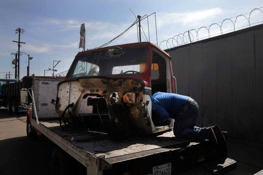 A man takes an old truck cab apart looking for pieces he can sell to a metal recycler in Los Angeles.