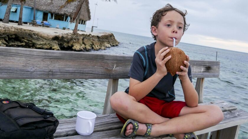 Reid Quirk sips on a freshly harvested coconut at sunset.