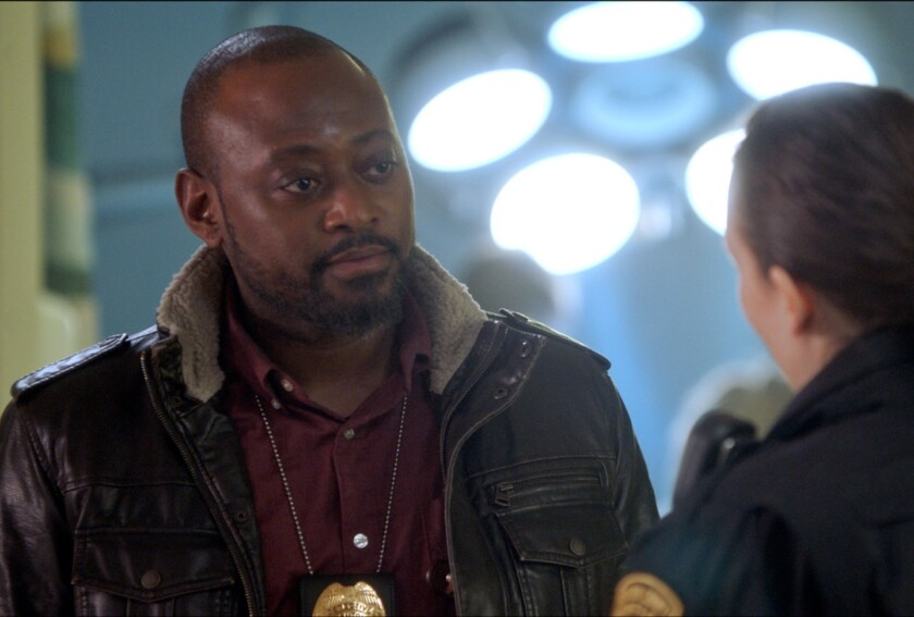 "Omar Epps as a police detective, with his badge on a chain around his neck, in ""Trick."""