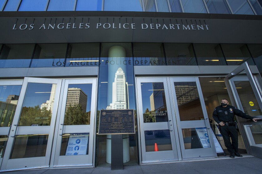 A LAPD officer wearing a face mask leaves police headquarters, where City Hall is reflected in a window.