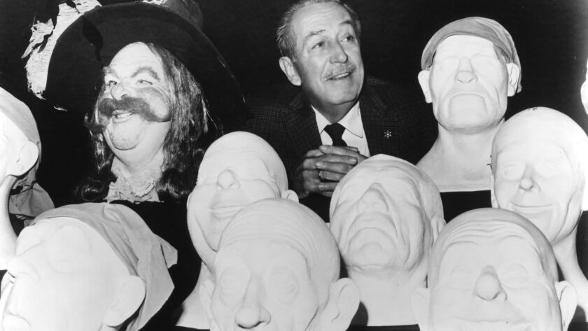 Walt Disney poses in 1966 with sculpted models that were used to create audio-animatronics figures for the Pirates of the Caribbean attraction, which opened on March 18, 1967, at Disneyland Park.