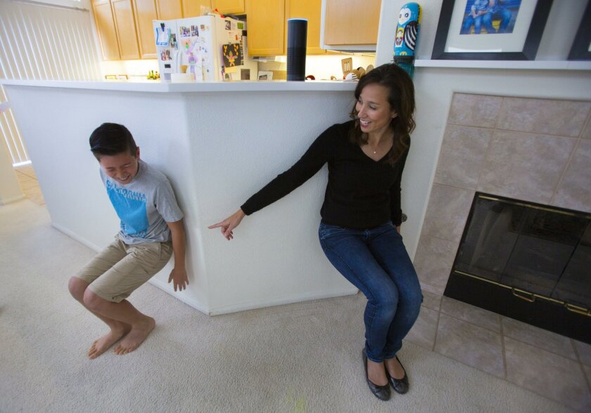 "10-year-old Greyson Philips, left, and his mom, Liz Philips, right, do a wall sit exercise as directed by ""Alexa,"" their Amazon Echo wireless speaker and voice command personal assistant at their Scripps Ranch home. One of the extra Alexa skills is a seven-minute workout."