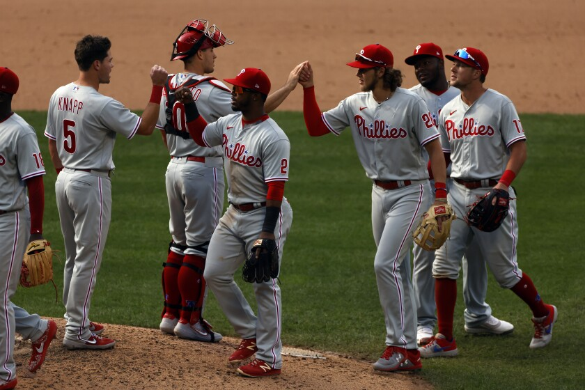 Philadelphia Phillies shortstop Jean Segura (2) celebrates with teammates after defeating the New York Mets in a baseball game on Monday, Sept. 7, 2020, in New York. (AP Photo/Adam Hunger)