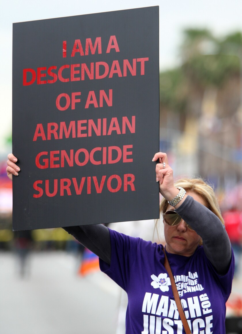 Vera Tchaghayan-Acun of Sun Valley holds a sign during the March for Justice commemorating the 100th anniversary of the Armenian Genocide, in this file photo taken Friday, April 24, 2015. The State Bar of California alleges a husband-and-wife legal team based in Glendale siphoned more than $300,000 of settlement money from a lawsuit over Armenian Genocide survivor benefits.