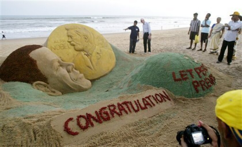 Visitors look at a sand sculpture of U.S. President Barak Obama with a Nobel Prize medal, created by sand artist Sudarshan Pattnaik on the Golden Sea beach in Puri, India, Saturday, Oct. 10, 2009. Obama won the 2009 Nobel Peace Prize on Friday. (AP Photo/Biswaranjan Rout)