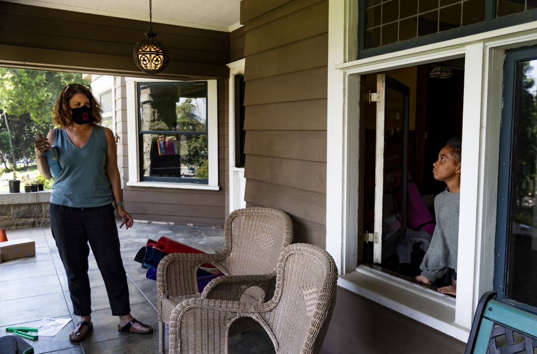 Former third-grade teacher Kristen Bristow listens to her daughter Andie, 6, on the porch of their Craftsman-style home.