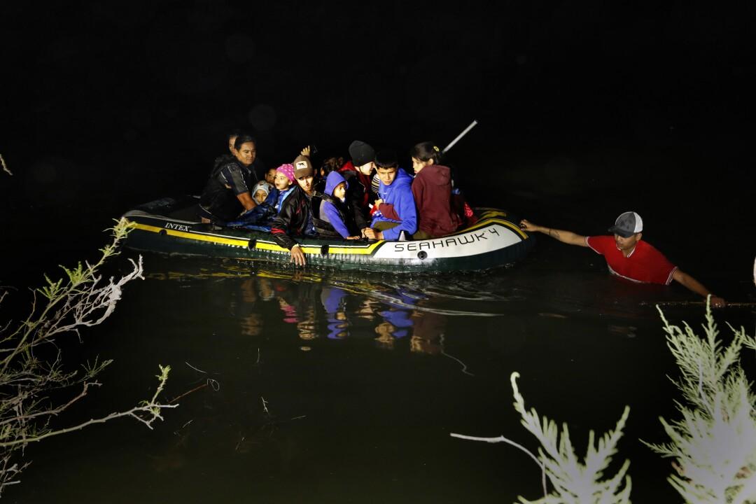 Asylum seekers cross the Rio Grande River in an inflatable raft