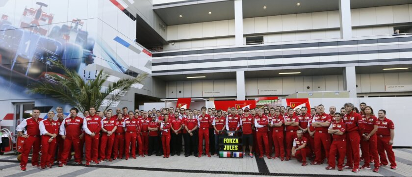 Ferrari team members pose for photographers with a banner reading 'Forza Jules' (Go Jules') in the paddock prior to the start of the Formula One Russian Grand Prix at the 'Sochi Autodrom' Formula One circuit, in Sochi, Russia, Sunday, Oct. 12, 2014. The Marussia Formula One team is running only one car at the inaugural Russian Grand Prix this weekend as a sign of respect for injured driver Jules Bianchi. The 25-year-old Bianchi suffered a severe head injury at last Sunday's Japanese Grand Prix in Suzuka and remains in critical condition in a hospital in Japan. (AP Photo/Luca Bruno)