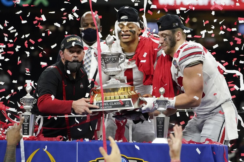 Ohio State head coach Ryan Day, from left, quarterback Justin Fields and linebacker Tuf Borland hold up the trophy after the team's win against Clemson in the Sugar Bowl NCAA college football game Friday, Jan. 1, 2021, in New Orleans. Ohio State won 49-28. (AP Photo/John Bazemore)