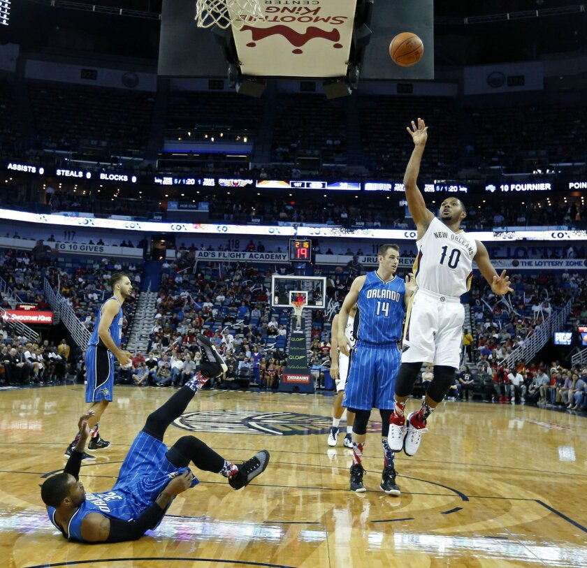 New Orleans Pelicans guard Eric Gordon (10) shoots as Orlando Magic guard C.J. Watson (32) falls to the court in the first half of an NBA basketball game in New Orleans, Tuesday, Nov. 3, 2015. (AP Photo/Gerald Herbert)