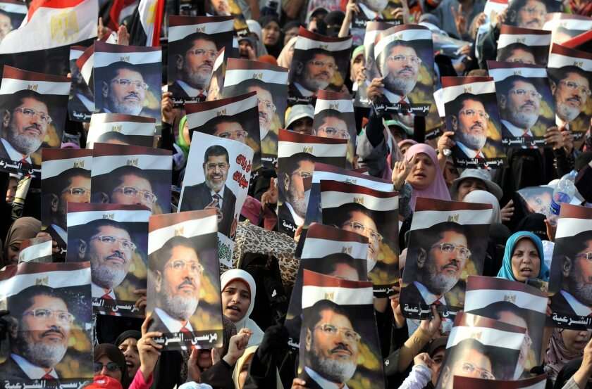 Demonstrators carry posters of Egypt's ousted president, Mohamed Morsi, outside a mosque in Cairo.