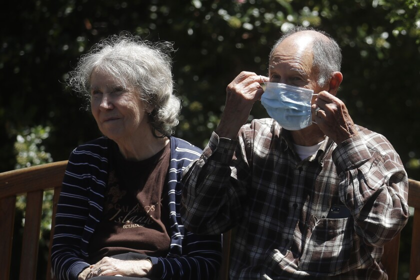 Larry Yarbroff, right, adjusts his mask as he sits with his wife, Mary, while visiting her at Chaparral House in Berkeley, Calif., Friday, July 10, 2020. For months, families have pined to see their loved ones in California's skilled nursing facilities, which have been shut down to outside visitors amid the coronavirus pandemic. California's health authorities recently issued guidance for visits to resume at these facilities, but so far, few appear to be happening as infection rates surge in many communities. (AP Photo/Jeff Chiu)