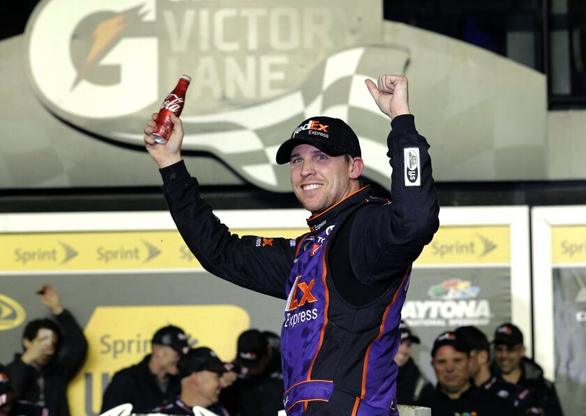 Denny Hamlin celebrates in Victory Lane after winning the Sprint Unlimited auto race at Daytona International Speedway, Saturday, Feb. 13, 2016, in Daytona Beach, Fla. (AP Photo/Terry Renna)