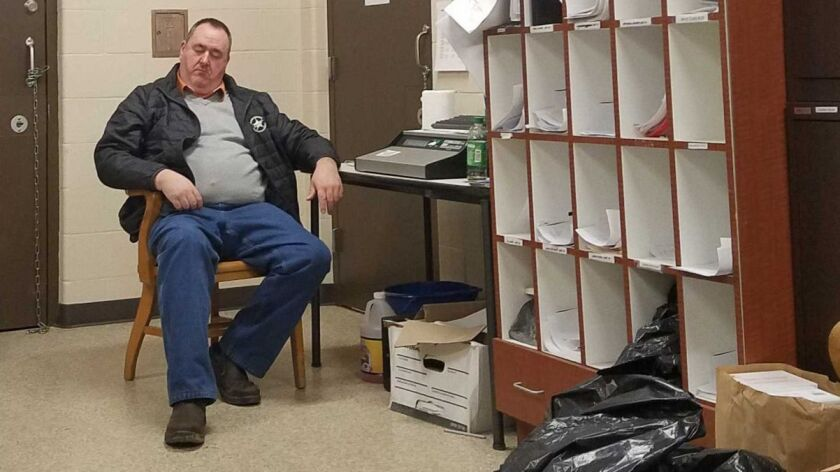 Martin County Sheriff John Kirk catchs a quick nap 14 hours into his shift. Kirk often works 16 hour