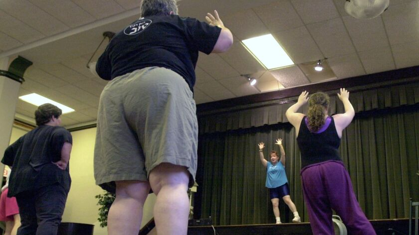 Overweight and obese people attend a fitness class in Lansdowne, Pa. Health experts are still debating whether it's more important to be fit or to get rid of excess fat.